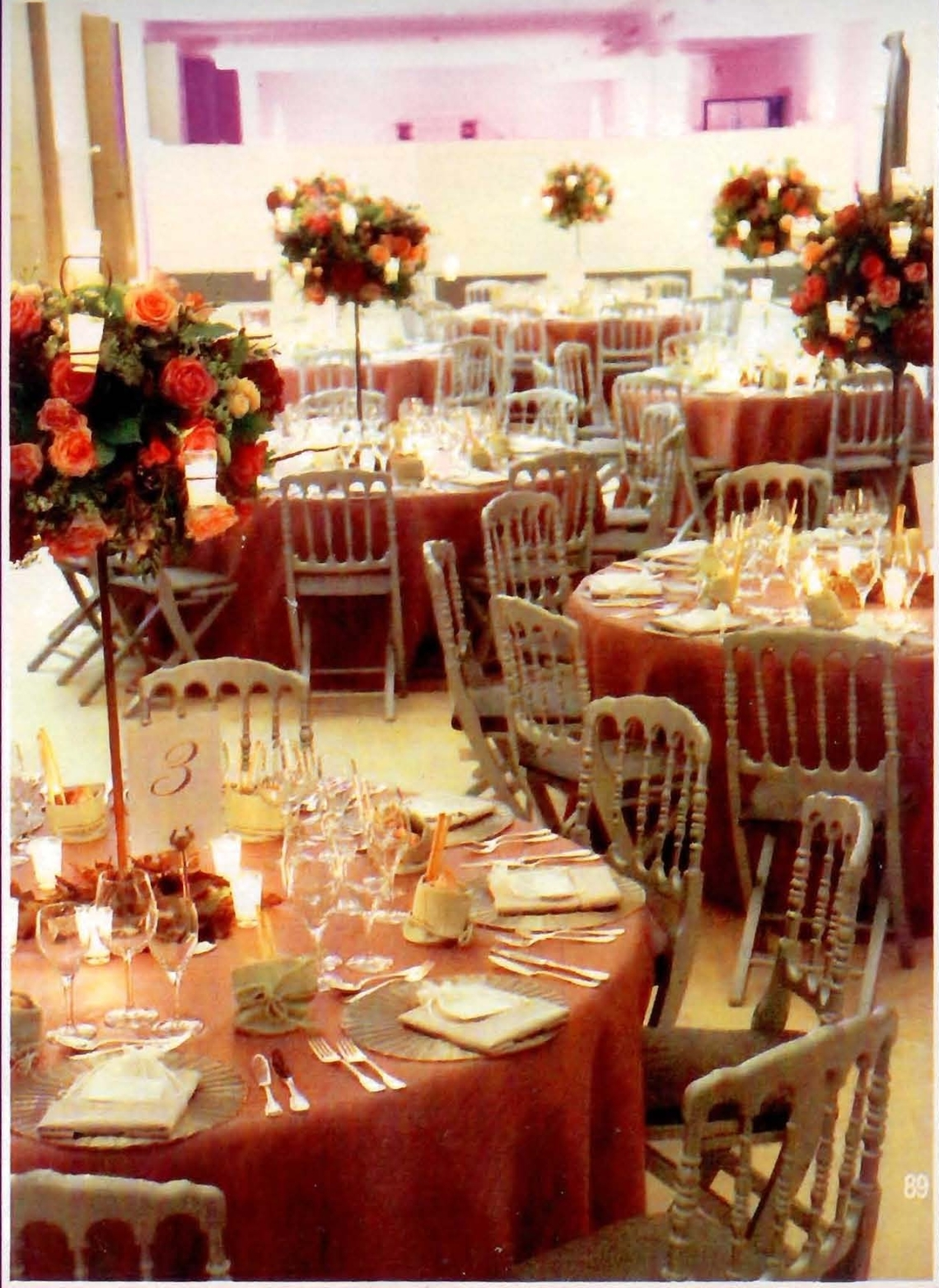 Mesas con sillas grises de palillería, manteles rosas y centros de mesas altos de rosas con velitas