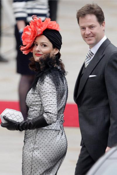 El Viceprimer Ministro, Nick Clegg y su mujer, Miriam González, con vestido de Miguel Palacio llegan a la Abadía para ocupar su sitio. Ella va muy llamativa con ese tocado en rojo.