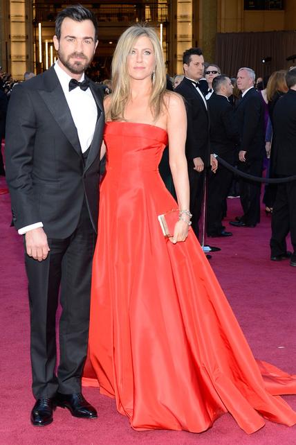 La que fuese la melena más codiciada de América, Jennifer Aniston, apostó por un rojo Valentino en palabra de honor y sonríe acompañada por Justin Theroux.