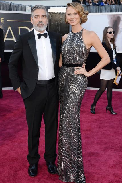Un barbudo George Clooney, nominado como productor de Argo, acompañado por Stacy Keibler, enfundada en un Naeem Khan