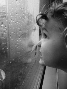 Niño mirando lluvia